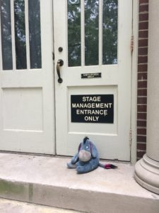 Eeyore sitting in front of the Stage Management Entrance